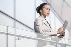 Beautiful young businesswoman holding digital tablet at office railing Stock Photography