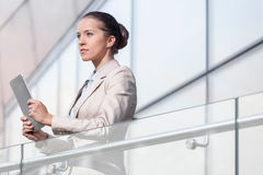 Beautiful young businesswoman holding digital tablet at office railing Stock Images