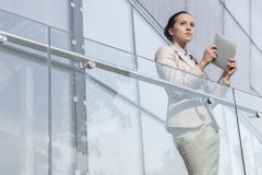 Beautiful young businesswoman holding tablet computer at office railing Stock Photography