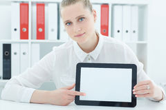 Beautiful young businesswoman holding tablet in hands sitting at office. Royalty Free Stock Photos