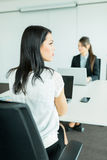 Beautiful young businesswoman looking away from the desk while h Stock Photo