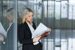 Beautiful young businesswoman looking documents in the office Royalty Free Stock Images