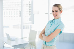 Beautiful young businesswoman posing with arms crossed in her office Stock Image