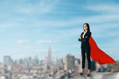 Confidence and power concept. Beautiful young businesswoman with red hero cape on rooftop with blurry city view and daylight. Confidence and power concept stock image