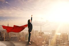 Confidence and superhero concept. Beautiful young businesswoman with red hero cape on rooftop with blurry city view and daylight. Confidence and superhero stock photos