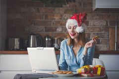 Beautiful young businesswoman in Santa Claus hat. Sitting and working with laptop. Concept of work with startup business in Christmas time Stock Photography