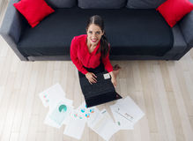 Beautiful young businesswoman sitting on the floor, using a laptop Royalty Free Stock Photo