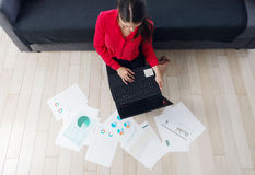Beautiful young businesswoman sitting on the floor, using a laptop Royalty Free Stock Image