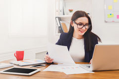 Beautiful young businesswoman sitting by office desk with laptop Royalty Free Stock Photo