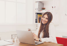 Beautiful young businesswoman sitting by office desk with laptop Stock Photo
