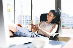 Businesswoman with a smartphone in her office. Beautiful young businesswoman with a smartphone in her office sitting with legs on desk Royalty Free Stock Photos