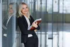Beautiful young businesswoman smiling and standing with folder in the office. looking at camera. copy space. Stock Image