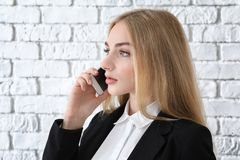 Beautiful young businesswoman speaking by mobile phone. Near white brick wall Stock Image