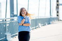 Beautiful happy young businesswoman using cell phone on city street. Beautiful young businesswoman using cell phone on city street royalty free stock images