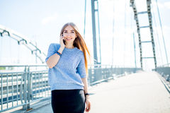 Beautiful happy young businesswoman using cell phone on city street. Beautiful young businesswoman using cell phone on city street royalty free stock photo