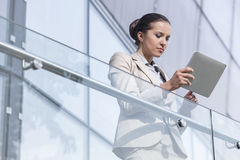 Beautiful young businesswoman using digital tablet at office railing Royalty Free Stock Images