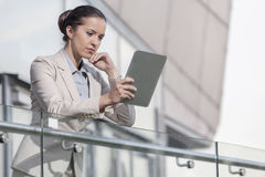 Beautiful young businesswoman using digital tablet at office railing Stock Photography