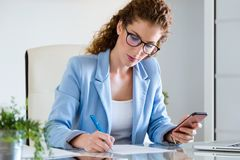 Beautiful young businesswoman using her mobile phone in the office. Royalty Free Stock Images