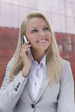 Beautiful young businesswoman using mobile phone against office building Royalty Free Stock Photography