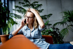 Beautiful young businesswoman using mobile phone while working. Royalty Free Stock Photos