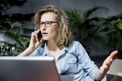 Beautiful young businesswoman using mobile phone while working with laptop. Royalty Free Stock Image
