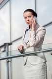 Beautiful young businesswoman using smart phone at office railing Stock Images