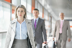 Beautiful young businesswoman walking with male colleagues in background at train platform Royalty Free Stock Images