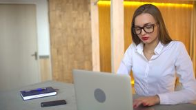 Close-up of beautiful businesslady working on laptop in office. 4 k. Beautiful young businesswoman wearing glasses and working at night using modern computer stock video