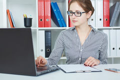 Beautiful young businesswoman working on a laptop in the office. royalty free stock photos