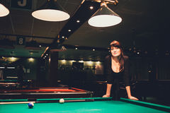 Beautiful young busty brunette woman playing billiard on red table indoors. Toned image. Warm atmosphere. Natural light. Stock Photography