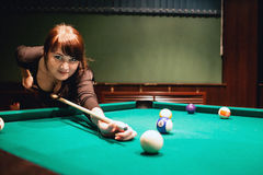 Beautiful young busty brunette woman playing billiard on red table indoors. Toned image. Warm atmosphere. Natural light. Royalty Free Stock Images