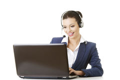 Beautiful young call-center assistant at the desk Royalty Free Stock Image