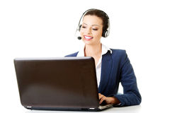 Beautiful young call-center assistant at the desk Royalty Free Stock Photos