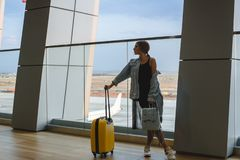 Beautiful young woman at the airport with a yellow suitcase and blue backpack. royalty free stock photography