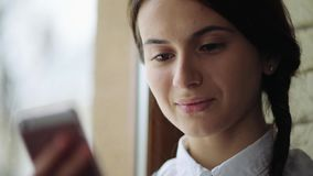 Beautiful young casual female using mobile phone and look at the window in her office. stock video footage