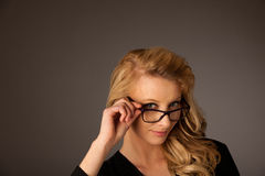 Beautiful young caucasian blond woman with eye glasses looking i Royalty Free Stock Photos