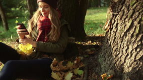 Beautiful young caucasian blonde girl sending sms texting in the autumn park. stock video footage