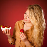 Beautiful young caucasian blonde woman holds a delicious fruit s Stock Photo
