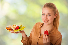 Beautiful young caucasian blonde woman holds a delicious fruit  Stock Photography