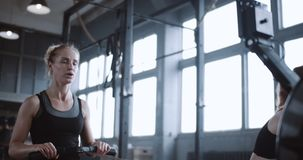 Beautiful young Caucasian blonde woman tired of exercising on rowing machine in gym with personal coach slow motion. Beautiful young Caucasian blonde woman tired stock video