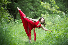 Beautiful young caucasian brunette woman in red dress outdoors, flexibility and stretching on nature. Beautiful young caucasian brunette woman in red dress Royalty Free Stock Images