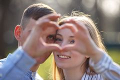 Couple looking through a heart made with  fingers. Beautiful young Caucasian couple close to each other looking through a heart made with their fingers Royalty Free Stock Image