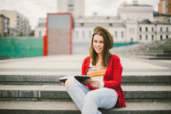 A beautiful, young Caucasian girl sitting on the street smile, the joy, sit with notebook and pen in Ruhi. In the red sweater, jea Stock Photo
