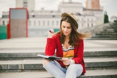 A beautiful, young Caucasian girl sitting on the street smile, the joy, sit with notebook and pen in Ruhi. In the red sweater, jea Royalty Free Stock Image