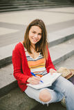 A beautiful, young Caucasian girl sitting on the street smile, the joy, sit with notebook and pen in Ruhi. In the red sweater, jea Stock Photography