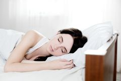 Beautiful young caucasian girl sleeping on bed. Light lifestyle interior in bedroom Royalty Free Stock Photography