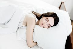 Beautiful young caucasian girl sleeping on bed. Light lifestyle interior in bedroom Stock Photography