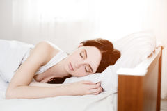 Beautiful young caucasian girl sleeping on bed. Light lifestyle interior in bedroom Royalty Free Stock Image
