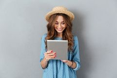 Beautiful young caucasian woman chatting by tablet. Picture of beautiful young caucasian woman chatting by tablet computer. Looking aside royalty free stock photo
