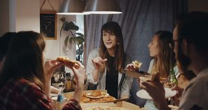 Beautiful young Caucasian woman eating pizza, talking and smiling with multiethnic friends at house party slow motion. stock video footage
